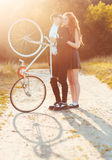 Guy with the girl and bicycle outdoors Stock Photos