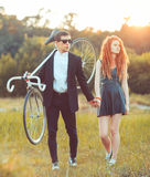 Guy with the girl and bicycle outdoors Royalty Free Stock Photography