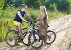 Teenagers in love ride bikes Stock Images