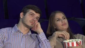 Cute couple bored while watching a movie at the cinema. The guy and the girl came to the cinema. They eat popcorn. The girl is very bored. The guy falls asleep stock footage