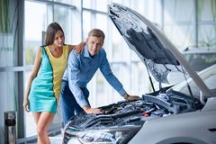 The guy with the girl came to the showroom to choose a new car. Royalty Free Stock Photos