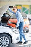 The guy with the girl came to the showroom to choose a new car. Stock Photography