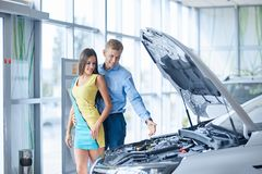 The guy with the girl came to the showroom to choose a new car. Royalty Free Stock Images