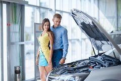 The guy with the girl came to the showroom to choose a new car. Royalty Free Stock Image