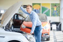 The guy with the girl came to the showroom to choose a new car. Royalty Free Stock Photography