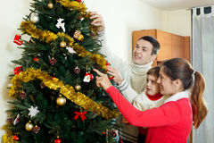 Guy and girl  with child preparing for Christmas. At home Stock Images