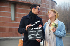 Guy and girl with clapperboard and money. Outdoor Stock Photo