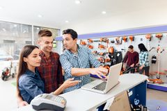 A guy and a girl with a consultant stand near the counter with a laptop. Royalty Free Stock Image