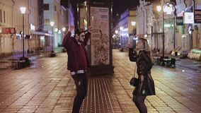 The guy and the girl are dancing in the middle of the night street. They are enjoying. A guy with a girl is walking around the night city. Lovers. Emotions stock video footage