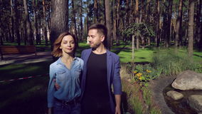 Guy and girl in denim clothes on the street. Happy couple enjoy stroll in park with beautiful spring landscape. thirties casual man and woman walking talking stock footage