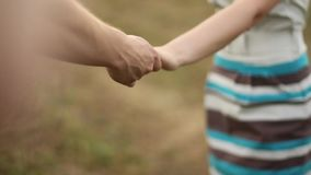 Guy and girl derzhutsja hands. Detail of two lovers joining hands stock video footage