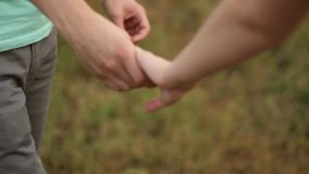 Guy and girl derzhutsja hands. Detail of two lovers joining hands stock footage
