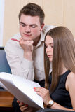 Guy and girl discuss new document Royalty Free Stock Image
