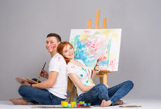 The guy and the girl draw paints. On the easel Royalty Free Stock Photo