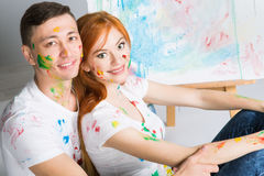 The guy and the girl draw paints. On the easel Stock Images
