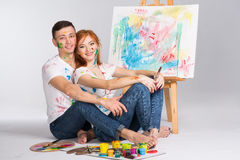 The guy and the girl draw paints. On the easel Royalty Free Stock Photography