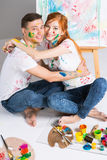 The guy and the girl draw paints. On the easel Stock Photography