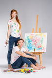 The guy and the girl draw paints. On the easel Stock Image