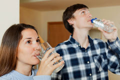 Guy and girl drinking bottled water Royalty Free Stock Images