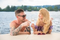 A guy with a girl is drinking champagne on a yacht. royalty free stock photography