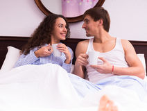 Guy and girl drinking tea and chatting in bed Royalty Free Stock Photo