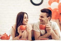 Guy And Girl Drinking Tea en cama Día del `s de la tarjeta del día de San Valentín imagenes de archivo