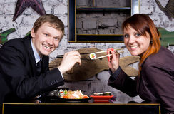 The guy with the girl eat sushi Royalty Free Stock Images