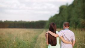 A guy with a girl embracing goes along a country road to the field. Sunset, Summer. stock footage