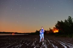 A guy with a girl stay on a beach at night royalty free stock images