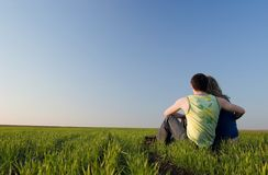 Guy and girl in the field. Guy embraces girl on a spring field. Low foreshortening Royalty Free Stock Photo