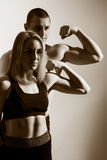 Guy and girl flex biceps. Stock Image