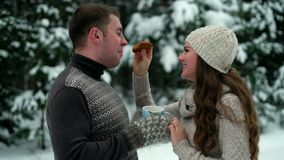 Guy and girl in the forest, drinking tea in winter stock video footage