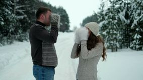 Guy and girl in the forest, drinking tea in winter stock footage