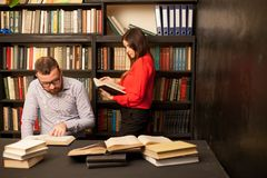A guy with a girl getting ready for the exam read books in the library Stock Photo