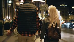 The guy with the girl go through the night city and talk. Rear view. Communication and emotions stock video footage