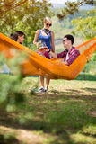 Guy and girl in hammock in nature toast with beer with female fr Stock Photography
