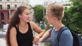 Guy and girl have fun talking on romantic date in city. Slow motion stock video footage