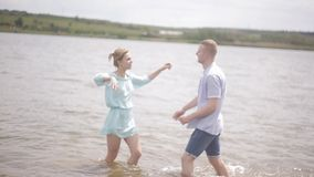 Loving couples have fun on the river bank. Romance, youth and a honeymoon. Happy guy and girl splashing water in the. The guy and the girl have fun in the water stock footage
