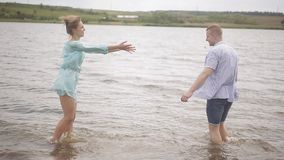 Loving couples have fun on the river bank. Romance, youth and a honeymoon. Happy guy and girl splashing water in the. The guy and the girl have fun in the water stock video
