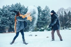 The guy and the girl have a rest in the winter woods. Husband and wife in the snow. Young couple walking in winter park. Royalty Free Stock Photography
