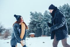 The guy and the girl have a rest in the winter woods. Husband and wife in the snow. Young couple walking in winter park. Stock Photography