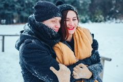 The guy and the girl have a rest in the winter woods. Husband and wife in the snow. Young couple walking in winter park. Royalty Free Stock Image