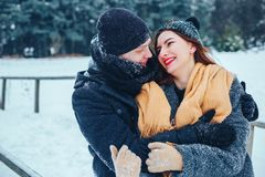 The guy and the girl have a rest in the winter woods. Husband and wife in the snow. Young couple walking in winter park. Stock Image