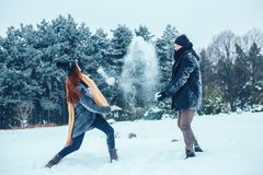 The guy and the girl have a rest in the winter woods. Husband and wife in the snow. Young couple walking in winter park. Royalty Free Stock Photo