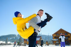 Guy and a girl are having fun in the courtyard of a cottage in a ski resort. royalty free stock images