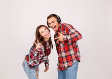 A guy with a girl in headphones shows two fingers and a tongue out on a gray background stock photography