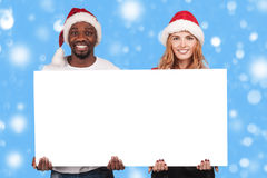 Guy and girl holding a white board with empty copy space for gre Royalty Free Stock Images