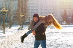 The guy and the girl indulge in the winter, he holds her on his shoulders and turns. A loving couple is playing outside. St. Valentine`s Day royalty free stock photos