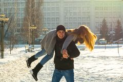 The guy and the girl indulge in the winter, he holds her on his shoulders and turns. A loving couple is playing outside. St. Valentine`s Day stock images