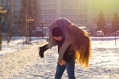 The guy and the girl indulge in the winter, he holds her on his shoulders and turns. A loving couple is playing outside. St. Valentine`s Day royalty free stock photography